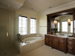 Bathroom remodel example featuring a large vanity, glass shower and corner bathtub