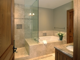 Bathroom example of a glass shower with a sitting ledge aside a built in corner bathtub