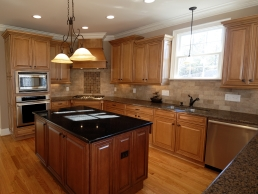 Kitchen remodel example featuring granite counter tops complimented by large wooden cabinets and hardwood floors