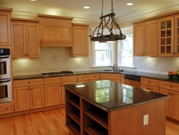 Kitchen remodel example featuring wooden cabinets with under cabinet lighting complimented by hard wood floors