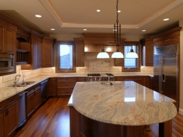 Kitchen remodel example featuring marble counter tops complimented by wooden cabinets and hardwood floors