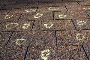 Insurance adjuster marking hail damage on roof.